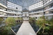 Work spaces at 4000 Connecticut Ave. NW look down onto an atrium with trees and water features.