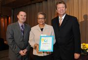 Alice Page of Reston Association, center, was present the award for the No. 1 Healthiest Employer for companies of 1 to 99 employees, by the WBJ's Doug Fruehling and Martin Lewis.