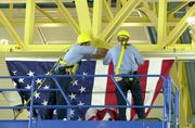 A crew hangs a flag at Reagan National Airport after the Sept. 11, 2001 attacks.