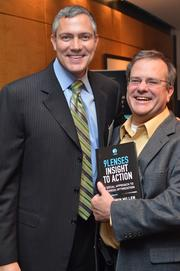 Edwin Miller, left, posed with Jonathan Wallace of WWC Capital Group and a copy of his book.