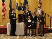 Lieutenant Jimmie Barrett Jr. stands with his family while receiving the Valor Award, presented by 2012 Chamber Chairman Doug Brammer and Arlington County Sheriff Beth Arthur.
