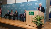 GMU President Alan Merten speaks at the dedication. Listening, from left, are student speaker Jacqueline Antonson, Arlington County Board Member Mary Hughes Hynes, CIA Director David Petraeus and Ed Rhodes, Dean of the School of Public Policy.
