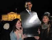 Two supporters hold a cutout of President Barack Obama outside the White House on Tuesday night.