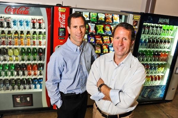 David Gordon, left, and Craig Kushner are stocking their vending machine business with a wireless network and hand-held devices that the company can use to determine when a machine is running low on a specific item.