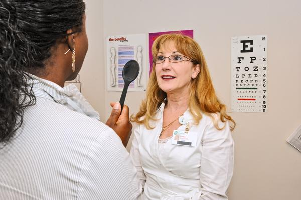 Quest-employed nurse Linda Pond, right, administers an exam to human resources staffer Erica Abram.