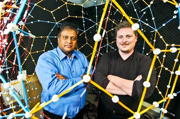 CEO Ramani Duraiswami and CTO Adam O'Donovan pose with a prototype made of toys for a product used for measuring 3-D sound.