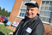 A volunteer shows his support for Mitt Romney at the Waterford precinct on the morning of Election Day.