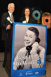Alex Orfinger, publisher of the Washington Business Journal, and Julia Huggins, President of CIGNA, Mid-Atlantic region, a premium sponsor, announce the winners at the 2012 Best Places to Work event.