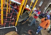 Volunteers pour concrete footings for the playground build on the grounds of DASH's Cornerstone Housing Facility on Saturday, Nov. 3.
