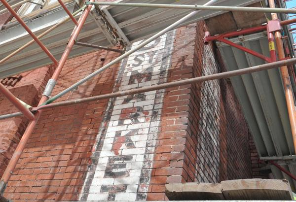 An original O Street Market sign was discovered under layers of age on the exterior brick of the market. It is now being redeveloped by Roadside Development.