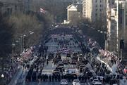 The presidential motorcade travels along the parade route during the inauguration. A crowd estimated by police to be as large as 700,000, including warmly dressed women with American flags stuck in their hair, a smattering of celebrities and many Republicans, gathered today to witness President Barack Obama take his second oath of office.