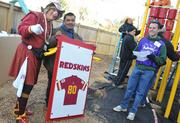 Volunteer Hogette Stonyette poses with staff at the playground build on the grounds of DASH's Cornerstone Housing Facility on Saturday, Nov. 3, where a panel in honor of the franchise's 80th anniversary was installed.