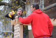 Volunteers put the finishing touches on an arbor over a bench at the playground build on the grounds of DASH's Cornerstone Housing Facility on Saturday, Nov. 3.