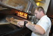 Bryan Voltaggio feeds the wood burning oven at his Range restaurant in the Chevy Chase Pavilion in Friendship Heights.