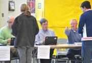 Volunteers at the Waterford precinct check photo IDs as voters check in  on the morning of Election Day.