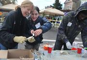 DASH Executive Director Peg Hacskaylo, left, and architect Meghan Walsh work on mosaic panels for the playground build on the grounds of DASH's Cornerstone Housing Facility on Saturday, Nov. 3.
