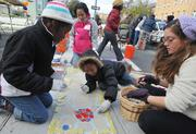 Children and volunteers work on mosaic panels for the playground build on the grounds of DASH's Cornerstone Housing Facility on Saturday, Nov. 3.