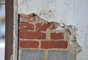 Years of paint and plaster is stripped away to reveal the original brick of the original O Street Market building.