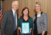 An Accenture PLC employee, center, accepts an award from Washington Business Journal Publisher Alex Orfinger and Juli Dennis, director of Wellness and Population Health Management at USI Insurance Services.