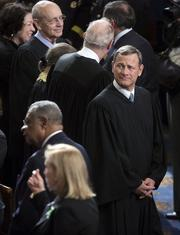 Supreme Court Chief Justice John Roberts, right, awaits the start of President Barack Obama's State of the Union address.