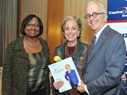 Colleen Taylor of Capital One and Alex Orfinger of the Washington Business Journal present award to honoree Joan Bialek at the 2012 Women Who Mean Business event.