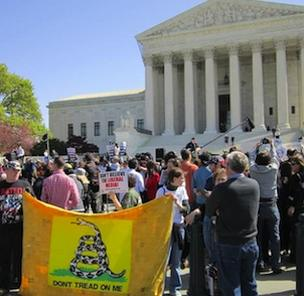 Demonstrators protest outside the U.S. Supreme Court as justices hear arguments over the constitutionality of the 2010 federal health care overhaul law.