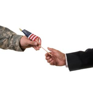Veteran handing businessperson a U.S. flag