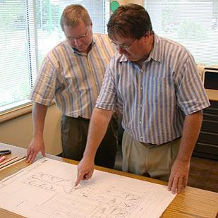 Mark Hutton, left, reviews blueprints for a past project in this file photo.