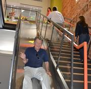 Larry Malone, who owns Howerton + White's building with his wife, Mary, enjoys a trip down the slide Thursday as the agency marked the completion of a renovation that added 3,500 square feet of work space.