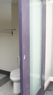 A sliding door with frosted glass for the bathroom.