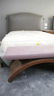 A new bed, still wrapped in plastic, and accompanying bench.