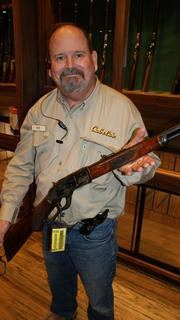 Rob Ellis, a Gun Library outfitter, shows an 1873 Winchester .32-.20-caliber rifle, one of many collectible guns in the library.