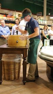 "Pam Rosencrans conducts a ceremonial ""Cracking of the Parmesan"" to mark the opening of The Fresh Market at Bradley Fair on Wednesday."
