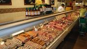 A butcher stands at the ready at The Fresh Market's meats department.