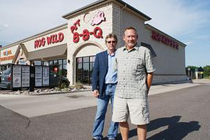 Gary Poulton, right, is owner of Hog Wild Pit Bar-B-Q. He's standing here with Curt Robertson of InSite Real Estate in 2009.