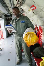 Tech. Sgt. Kevin Toney demonstrates how to use the KC-135's oxygen masks. The masks provide a seal around a person's entire head to protect against any fuel fumes.