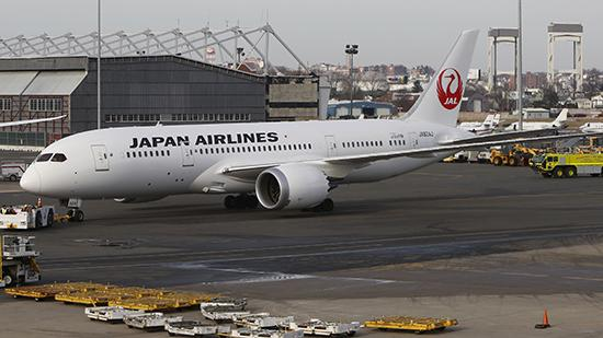 A Boeing Co. 787 Dreamliner jet operated by Japan Airlines Co. is towed back to the gate at Logan International Airport in Boston Tuesday morning. The plane leaked fuel while taxiing for departure.
