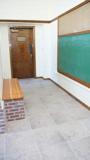 The kindergarten unit includes a bench and chalkboard near its entry.