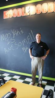 """Mooyah franchisee Anthony Powell stands next to the floor-to-ceiling """"Moodle Doodle"""" chalkboard on which children can draw to their hearts' delight. A flat-screen TV near the board can be tuned to cartoons for tots, too."""