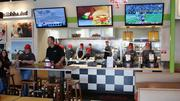 Mooyah franchisee Anthony Powell, under the TV at left, answers questions as kitchen staff prepare for the lunch rush about to begin. Five flat-screen TVs are tuned to everything from The Weather Channel to Sports Center to CNN news, with one dedicated to Mooyah messages.