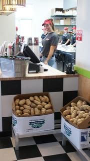 Kathryn Reichenberger, a Mooyah guest specialist, is ready to take orders Monday. Those potatoes? They're becoming fries.