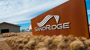 Brokerage firm Wunderlich Securities has downgraded SandRidge Energy Corp. based on planned asset sales, concerns about the company's management and uncertainty on the Mississippian Lime play in Kansas and Oklahoma.