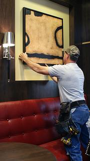 Kevin McBrayer of Arden & Associates in Oklahoma City hangs a picture inside the bar, located just off the Siena Tuscan Steakhouse.