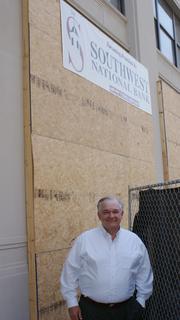 Ron Heikes, senior vice president-commercial lending for Southwest National Bank, stands below the prominent banner along Douglas Avenue advertising the bank's role in the Ambassador Hotel project.