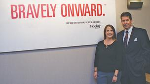 Al Sanchez, senior vice president-marketing at Fidelity Bank, and Katie Grover, assistant vice president-brand manager, stand in front of a poster trumpeting the bank's new message.