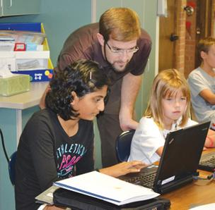 Collegiate sixth-graders Vasuma Chaparala, left, and Lauren Caughlin work with Troy Fischer to set up their laptop computers Monday at Wichita Collegiate. The school issued 500 computers this year.