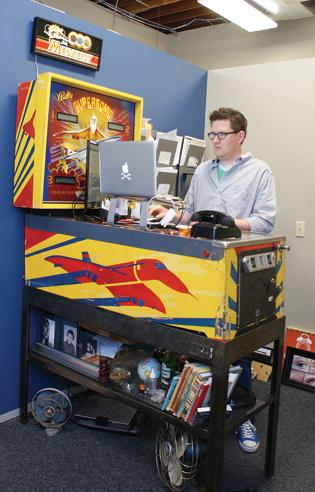 Kenton Hansen's standing desk at Apples & Arrows marketing agency is a pinball machine with a base that makes the surface level.
