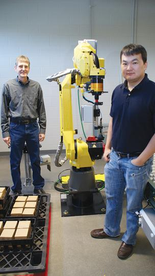 Robotics instructors Bruce Handyside, left, and Enkhsaikhan Boldsaikhan show one of the robotics program robots, a Fanuc M-20.