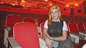 Orpheum President Jennifer Wright sits in one of the dated auditorium seats in the historic theater at 200 N. Broadway. Replacing those seats is just one aspect of a potential plan to finish restoring the theater.