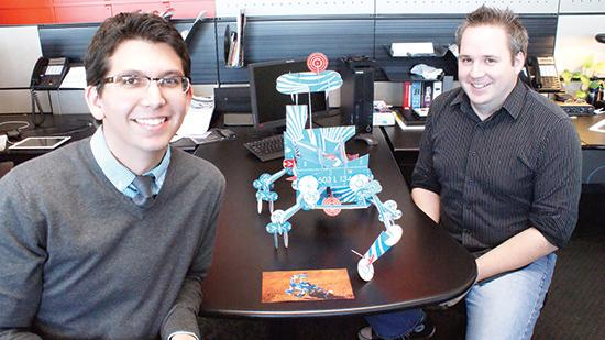 "Landon Barton, left, and Seth Duncan of Greteman  Group show off the Mars rover they created from the agency's ""Gift of Lift"" kit."